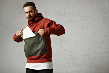 anorak: Attractive male model taking a blank white sheet of paper out of the front pocket of his red and gray parka on white background