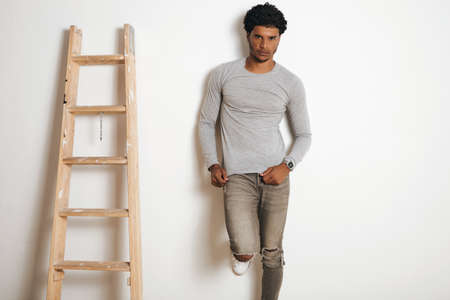 Serious attractive latino man wears blank grey longsleeve and poses near ladder , isolated on white Stock Photo