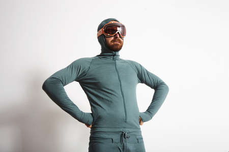 wears: Young fitted bearded male athlete in baselayer thermal suite wears snowboarding googles, proudly stands in front of white wall