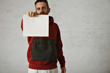 anorak: A man in red and grey anorak holds a blank white sign to the camera in a studio with white walls