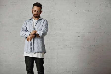 rolling up: Young bearded hipster rolling up a sleeve of his casual light denim shirt showing tattoos on his arm in a studio with white brick walls
