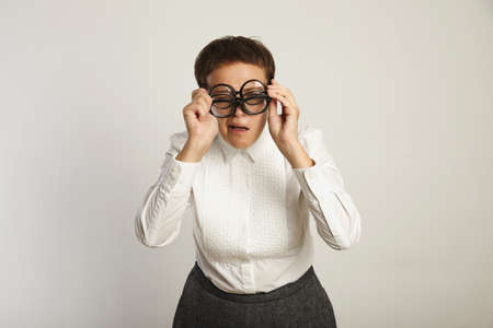 weird: Weird female teacher trying to see through three pairs of glasses isolated on white LANG_EVOIMAGES