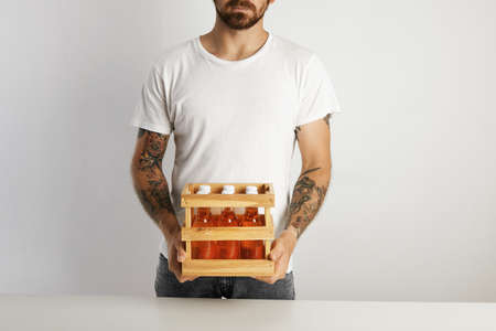 unmarked: Bearded and tattooed man holding a small crate with six unmarked glass bottles of craft lager beer drink against white wall background