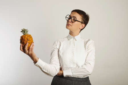 conservative: Crazy looking teacher in conservative outfit looking inquiringly at a pineapple isolated on white LANG_EVOIMAGES