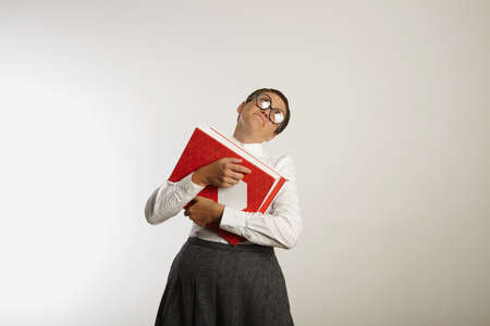conservative: Tired looking female teacher in conservative clothes almost falls down under the weight of heavy binders against white wall background