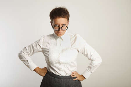 conservative: Angry female teacher in round black glasses and conservative outfit frowning isolated on white