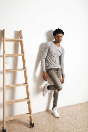Serious latino dark skinned man wears blank heather grey clothing and pose near wooden ladder on white wall, side view Stock Photo
