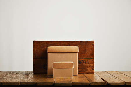 contrasted: New beige cardboard boxes contrasted against a vintage wine crate and a brown rustic table isolated on white
