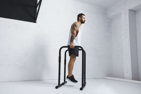 Strong tattooed in white unlabeled tank t-shirt male athlete shows calisthenic moves Holding position on parallel bars before classic dips, looking straight