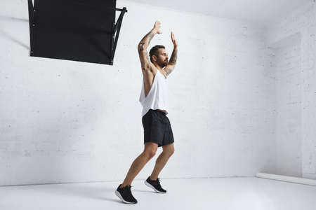 jacks: Tattooed and muscular athlete doing jumping jacks isolated on white brick wall next to black pull bar, looking right side