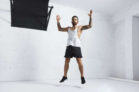 Tattooed and muscular athlete doing jumping jacks isolated on white brick wall next to black pull bar, looking left side