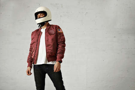 bomber: Young attractive male model in black jeans, plain white t-shirt, burgundy nylon bomber jacket and a white motorcycle helmet