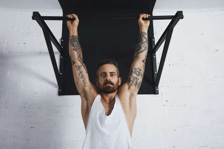 Brutal tattooed athletic man in white unlabeled tank t-shirt shows calisthenic moves close up of classic pullup Hanging on pull bar and looking at camera.