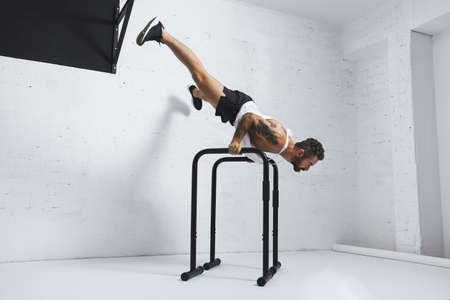 Strong tattooed in white unlabeled tank t-shirt male athlete shows calisthenic moves Extended legs planche push ups on parallel bars LANG_EVOIMAGES