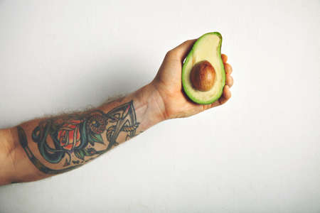 man's: Close up shot of a tattooed mans arm with a half of ripe fresh avocado isolated on white