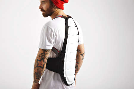 the protector: Back of a serious muscular young man with tattoos wearing snowboarding back protector isolated on white