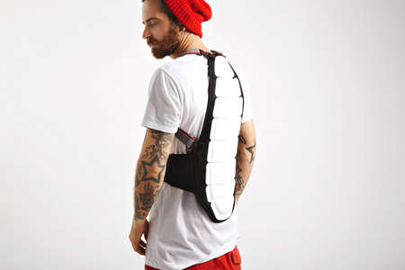 the protector: Serious bearded and tattooed snowboarder in white t-shirt and red beanie wearing white and black back protector isolated on white LANG_EVOIMAGES