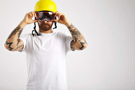 halfpipe: Serious focused young man in snowboarding helmet and unlabeled white t-shirt putting on goggles looking straight into the camera in studio with white walls