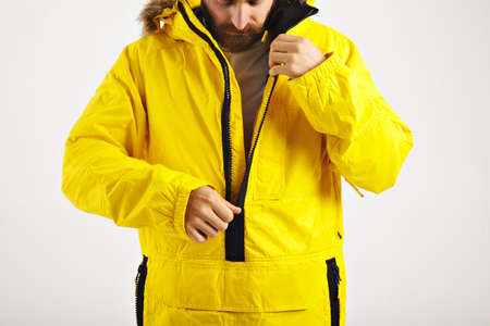 Serious bearded young man zipping up his bright yellow warm snowboarding anorak isolated on white LANG_EVOIMAGES