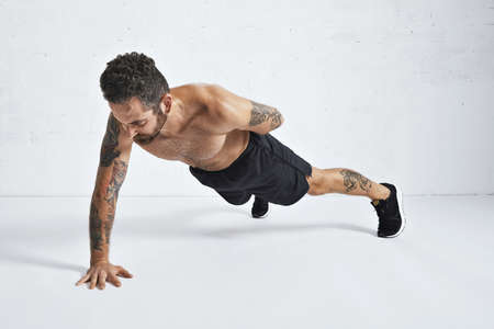 Strong brutal tattoed and ripped male athlete shows how to do one hand push-ups, isolated on white spacious gym, top position LANG_EVOIMAGES