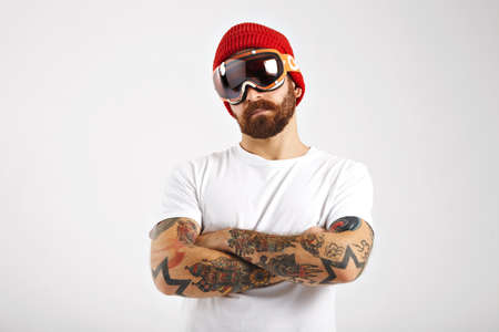 Portrait of a fit young man wearing a red knitted hat, skiing goggles and a plain white t-shirt isolated on white