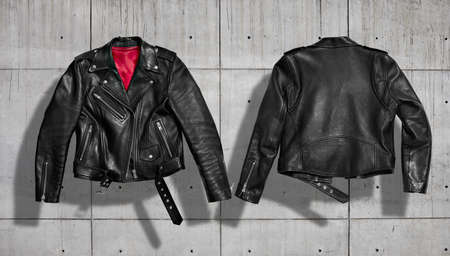 Classic women black leather bikers' jacket with silk red lining shot from the front and the back isolated on neutral indastrial concrete gray background