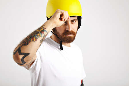 halfpipe: Serious tattooed and bearded young man looking into camera and adjusting his plain yellow snowboarding helmet isolated on white