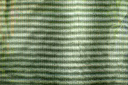Background image with slightly wrinkled green and white traditional checkered tablecloth
