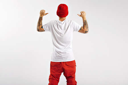 Back shot of an attractive athletic tattoed snowboarder in red and white clothing pointing to his plain cotton t-shirt shot from the back on white background