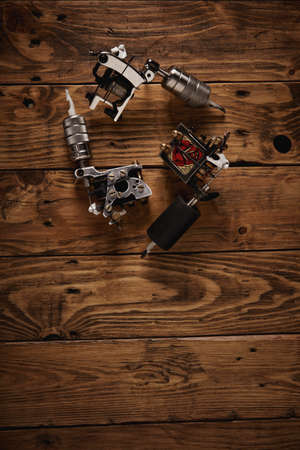 traditional custom: Three different custom hand made electric traditional professional tattoo guns arranged on a brown wooden table