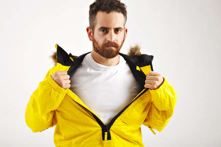 Sexy bearded young man showing plain white t-shirt under his bright yellow snowboarding jacket isolated on white