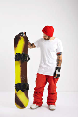 A young snowboarder wearing red pants, white unlabeled t-shirt and red beanie looking at his snowboard in studio with white walls LANG_EVOIMAGES