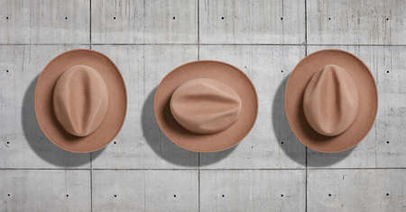 rotations: Classic felt beige fedora hat shot from the top in three different rotations as a set isolated neutral gray concrete industrial background