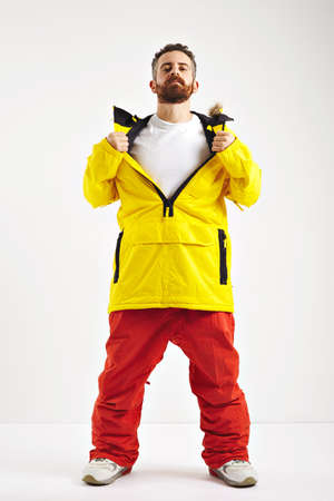 anorak: Snowboarder in red pants and yellow anorak opening up the front of his jacket to show plain white cotton t-shirt isolated on white