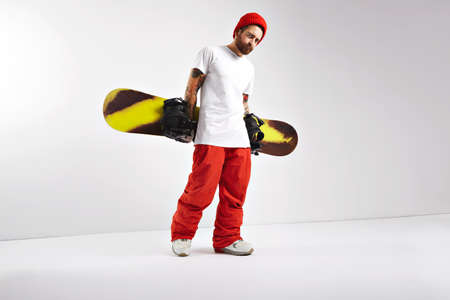 tattoed: Rough muscular tattoed snowboarder in bright clothing and oversized blank white t-shirt walking with his snowboard behind his back isolated on white