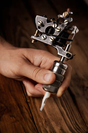 Close up of a mans hand with a professional custom made induction tattoo gun Stock Photo