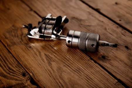 Close focus on shiny steel chrome handmade traditional induction tattoo gun on rustic wooden table