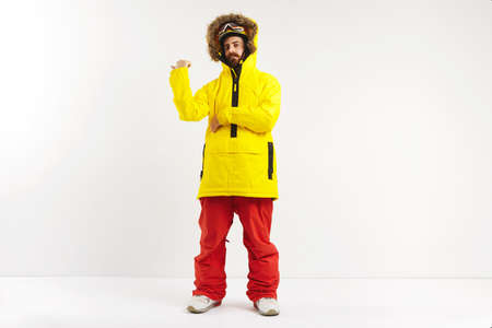 Fashionable fit snowboarder in bright yellow coat and red pants pointing behind his back while looking into the camera in a studio with white walls LANG_EVOIMAGES