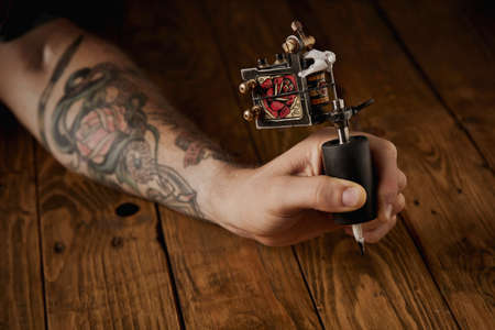 arms trade: Close up of a mans hand presented new custom made induction tattoo gun for coloring with rose graphic