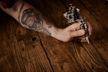 Close up of a mans hand holds new custom made steampunk style tattoo gun above brushed vintage wooden table LANG_EVOIMAGES