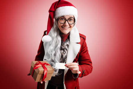 gray hairs: Mrs Claus happily smiling with gray hairs, weraing Santa hat, traditional sweater, round glasses and red warm coat holds beautiful craft box with holiday christmas gift inside and name tag on it, looking on camera. LANG_EVOIMAGES