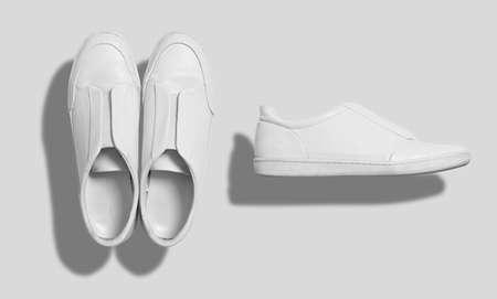 White leather sneaker like casual shoes with flat sole without shoelaces shot from the top and from the side isolated on white