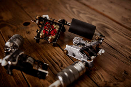 Close up on three custom made professional induction tattoo machines arranged in round on a brown wooden table