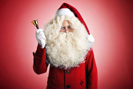 Serious looking Santa with large white beard wearing a fashionable red coat ringing a shiny gold bell isolated on red