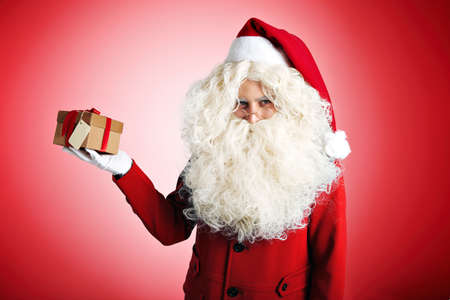 Trendy Santa in nice red clothes with huge white beard holding a present in craft cardboard box with red ribbon on red background