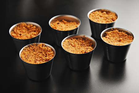 apple crumble: Six portions of apple crumble dessert in individual steel cups on shiny black table