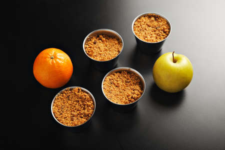 homestyle: Presentation of four identical stainless steel cups with apple crumble dessert, one orange and one yellow apple shot from the top on black table LANG_EVOIMAGES
