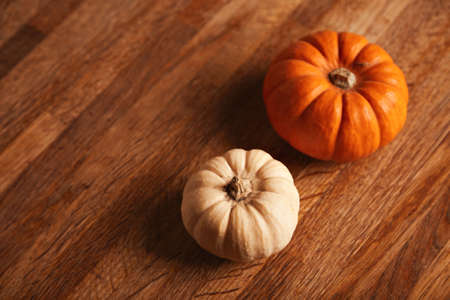 Two miniature and tasty decorative pumpkins of different colors on rustic brown table