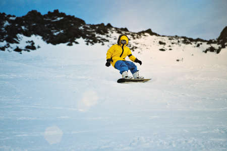 Man rides his snowboard very fast, making carved turns on backside edge, on ski slope in winter mountains, in ski resort