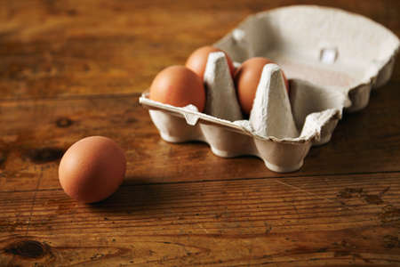 Close up shot of an open recyclable egg carton with 3 eggs inside and one egg next to it on a brown grainy wooden table Ecological healthy food from bio farms. LANG_EVOIMAGES